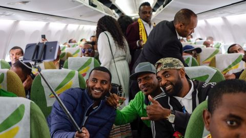 Passengers pose for a selfie picture inside an Ethiopian Airlines flight who departed from the Bole International Airport in Addis Ababa, Ethiopia, to Eritrea's capital Asmara on July 18, 2018. - The first commercial flight to Eritrea in two decades departed on July 18, 2018 from Addis Ababa after the two nations ended their bitter conflict in a whirlwind peace process. (Photo by Maheder HAILESELASSIE TADESE / AFP)        (Photo credit should read MAHEDER HAILESELASSIE TADESE/AFP/Getty Images)