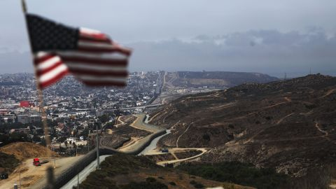 SAN DIEGO, CA - JULY 16:  An American flag flies along a section of the U.S.-Mexico border fence on July 16, 2018 in San Diego, California. The entire Southwest border saw 34,114 U.S. Border Patrol apprehensions in the month of June compared with 40,338 in May.  (Photo by Mario Tama/Getty Images)