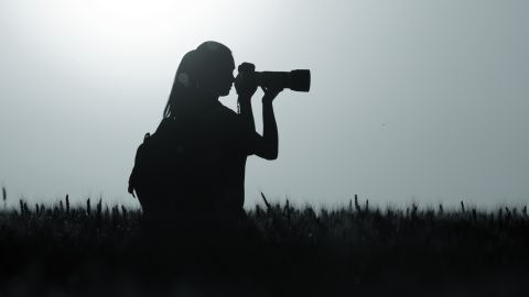 Silhouette of young girl taking nature photos in wheat field at night