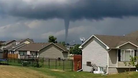 A tornado destroying a home, a tornado above a man's home and a third tornado to the left in Bondurant, IA.
