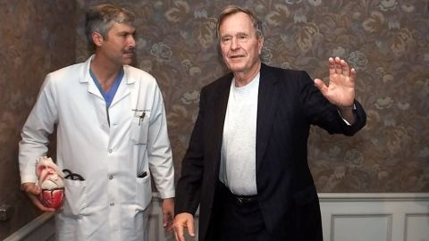 Former President George Bush, center, waves as he leaves with cardiologist Mark Hausknecht, left, and Bush's family doctor Ben Orman, right, after a news conference at Methodist Hospital Friday, Feb. 25, 2000 in Houston. Bush spent Thursday night in a Florida hospital and was released Friday after being treated for atrial fibrillation. He returned to Houston Friday and was admitted to Methodist Hospital for further tests. (AP Photo/David J. Phillip)
