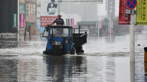 A local drives through a flooded street caused by heavy rainstorms in Harbin city, northeast China's Heilongjiang province on July 19.