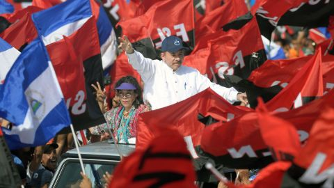 """Nicaraguan President Daniel Ortega (R) and his wife, Vice President Rosario Murillo (L), wave to supporters during the commemoration of the 39th Anniversary of the Sandinista Revolution at """"La Fe"""" square in Managua on July 19, 2018. - Nicaragua's President Daniel Ortega on Thursday marked the 39th anniversary of the Sandinista revolution's victory that first brought him to power after intensifying a deadly crackdown on protesters demanding he step down. (Photo by MARVIN RECINOS / AFP)        (Photo credit should read MARVIN RECINOS/AFP/Getty Images)"""