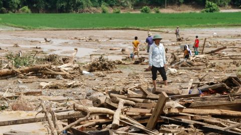 Residents clear debris in a village damaged by flash flooding in Vietnam's Yen Bai province on Saturday.