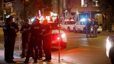 Toronto Police officers walk the scene at Danforth St. at the scene of a shooting in Toronto, Ontario, Canada on July 23, 2018. - A gunman opened fire in central Toronto on Sunday night, injuring 13 people including a child. Two dead incluiding gunman, police reported. (Photo by Cole BURSTON / AFP)        (Photo credit should read COLE BURSTON/AFP/Getty Images)