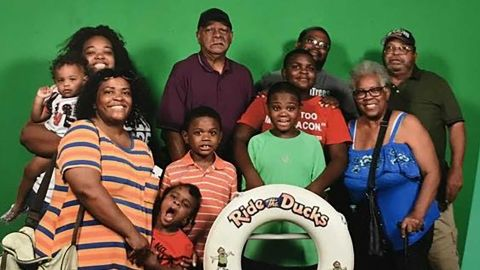 Tia Coleman and 10 of her relatives got on a duck boat to take a tour of Table Rock Lake during their family vacation. Of those relatives, only she and her nephew survived when the boat sank.  Back, left to right: Tia Coleman, holding her 1-year-old Arya, Ray Coleman, Glenn Coleman (husband), Horace Coleman.   Front: Angela Coleman, Max, Evan (striped shirt), Reece (green shirt), survivor Donovan Hall (behind Reece), Belinda Coleman.