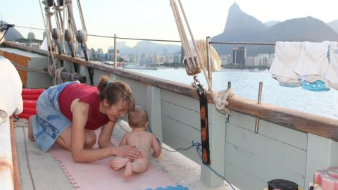 """Theo lived aboard The Lista Light from the age of three months to almost a year. He's pictured playing on deck, with Rio de Janeiro in the background. """"We let him walk and crawl around on deck when it was calm, but one of us was always close,"""" said Katharine. """"His balance was amazing -- he could stand up holding on to the swaying fencing."""""""