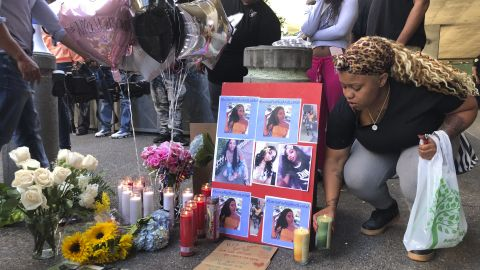 Malika Harris places a candle down for her sister Nia Wilson at a makeshift memorial outside the MacArthur Bay Area Rapid Transit station, Monday, July 23, 2018, in Oakland.