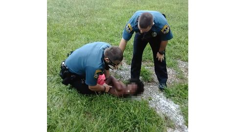 An image taken from a Facebook video shows two officers restraining a 10-year-old boy.