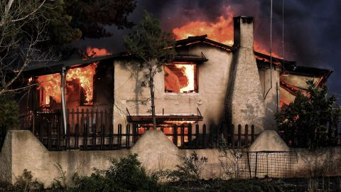 A house burns in a wildfire in Kineta on Monday, July 23.