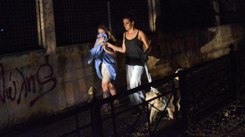 Two women evacuate Mati on July 23.