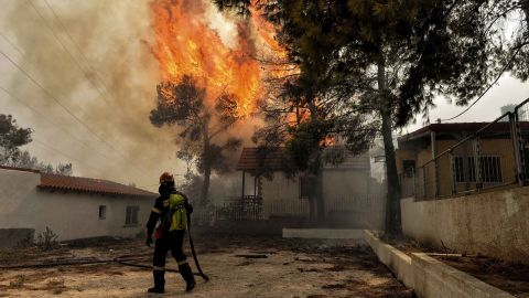 """TOPSHOT - A firefighter tries to extinguish hotspots during a wildfire in Kineta, near Athens, on July 23, 2018. - More than 300 firefighters, five aircraft and two helicopters have been mobilised to tackle the """"extremely difficult"""" situation due to strong gusts of wind, Athens fire chief Achille Tzouvaras said. (Photo by VALERIE GACHE / AFP)        (Photo credit should read VALERIE GACHE/AFP/Getty Images)"""