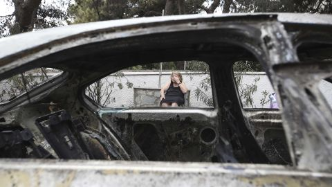 Asimina Psalti, 87, sits outside the remains of her burned house in Mati on July 24.