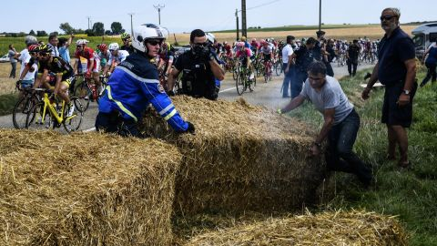Gendarmes remove haystacks that were placed on the stage's route.