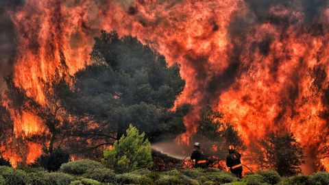 Firefighters try to extinguish wildfire flames in Kineta, Greece, on Tuesday, July 24.