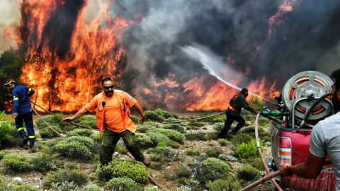 Firefighters and volunteers try to extinguish flames during a wildfire at the village of Kineta, near Athens, on July 24, 2018. - Raging wildfires killed 74 people including small children in Greece, devouring homes and forests as terrified residents fled to the sea to escape the flames, authorities said Tuesday. (Photo by ANGELOS TZORTZINIS / AFP)        (Photo credit should read ANGELOS TZORTZINIS/AFP/Getty Images)
