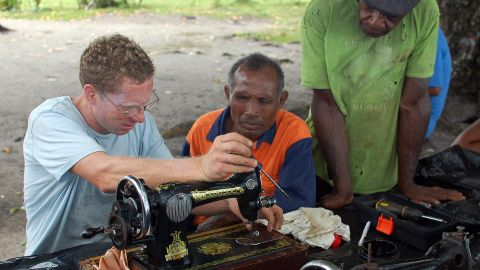 During their travels, the Giffords have exchanged time on the boat and other acts of goodwill for recipes and cultural experiences. Here Jamie helps a local in Papua New Guinea repair a sewing machine.