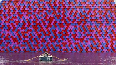 <strong>London, UK: </strong>As a heatwave hits the UK capital, a woman rows past the London Mastaba, a floating sculpture created by Romanian artist Christo in the Serpentine lake in Hyde Park.