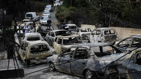 Burnt cars are seen in Mati following the wildfire.