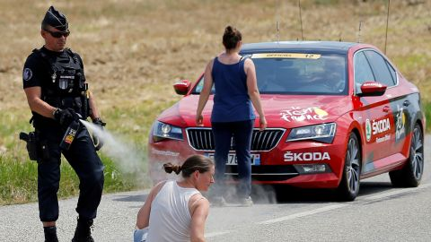 """A police officer sprays tear gas at one protester as another protester stands in front of the race director's car on July 24. Protesting farmers had blocked the road with hay bales, and <a href=""""https://www.cnn.com/2018/07/24/sport/tour-de-france-protesters-pepper-spray/index.html"""" target=""""_blank"""">the race was temporarily halted</a> after tear gas inadvertently got into the eyes of some riders."""