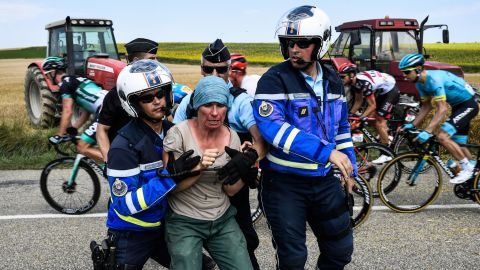 Gendarmes detain a protesting farmer as the pack rides behind them.