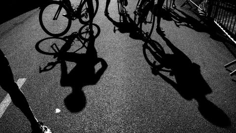 Riders' shadows are seen near the finish line after the 15th stage.