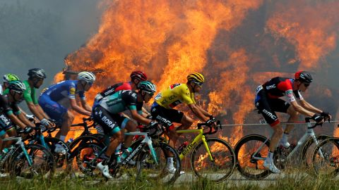 A pack rides by a burning haystack during the sixth stage on July 12.