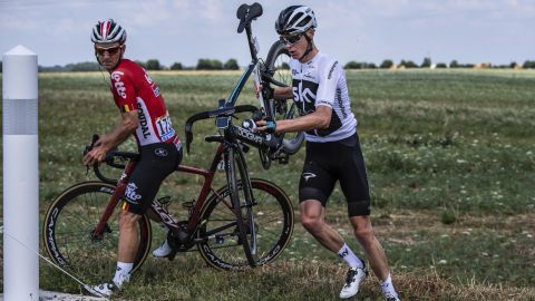 Belgium's Jasper De Buyst, left, and Britain's Chris Froome get back on the road after crashing during the first stage on July 7. Froome is the defending champion.