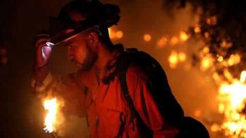 A firefighter monitors a backfire while battling the Carr Fire on July 27. The fire grew rapidly, ravaging several small communities and jumping the Sacramento River before threatening the outskirts of Redding.