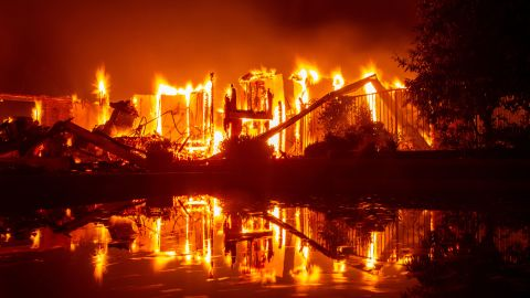 A burning home is reflected in a pool in Redding on July 27.