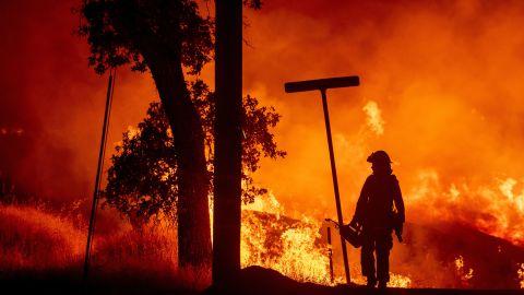 A firefighter lights backfires in Redding on July 27.