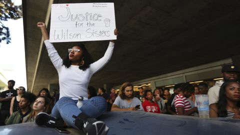 Jasmine Malone, 23, holds a sign at a vigil held for 18-year-old Nia Wilson, who was stabbed to death the night before at the MacArthur BART station in Oakland, California, on Monday, July 23, 2018.