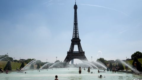 People cool themselves at the Trocadero Fountain, in front of the Eiffel Tower in Paris on Friday, July 27.