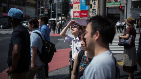 """A man in Tokyo shields his eyes from the sun on Tuesday, July 24. Dozens of people have died across Japan as the country continues to swelter under <a href=""""https://www.cnn.com/2018/07/23/asia/japan-heatwave-deadly-intl/index.html"""" target=""""_blank"""">scorching summer temperatures.</a>"""