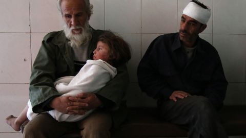 A man holds a wounded child at a hospital in Eastern Ghouta following airstrikes on November 15, 2017.