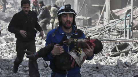 A member of the White Helmets volunteer rescue group carries an injured child after airstrikes in Eastern Ghouta on February 19.