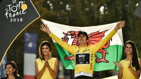 Tour de France 2018 winner Geraint Thomas  holds the Welsh flag as he celebrates on the podium in Paris.
