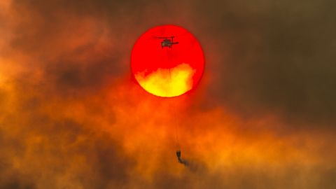 In this Friday, July 27, 2018 photo, a firefighting helicopter makes a water drop as the sun sets over a ridge burning near Redding, Calif., in efforts against the Carr Fire. Scorching heat, winds and dry conditions complicated firefighting efforts. (Hector Amezcua/The Sacramento Bee/ AP