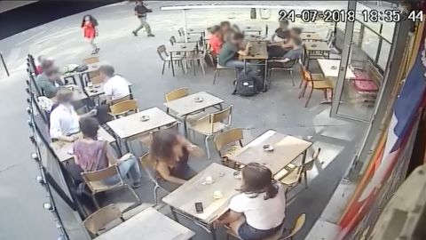A screengrab from CCTV footage at a cafe in Paris shows an interaction between a woman and a man who *allegedly* harassed her. CNN has applied a light blur to the faces of bystanders to protect their identities.
