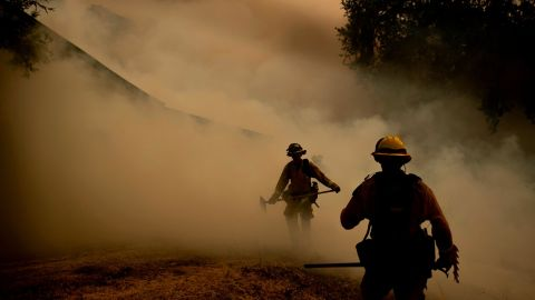 A firefighter walks through smoke while fighting to save a winery in Lakeport on July 30.