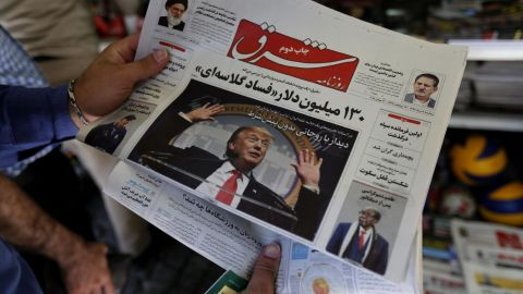 A man takes a glance at a newspaper with a picture of US president Donald Trump on the front page, in the capital Tehran on July 31, 2018. (Photo by ATTA KENARE/AFP/Getty Images)
