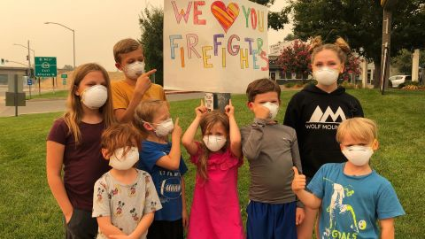 Nichole Grubbs-Miller and her sister's children handmade signs thanking firefighters for their service.