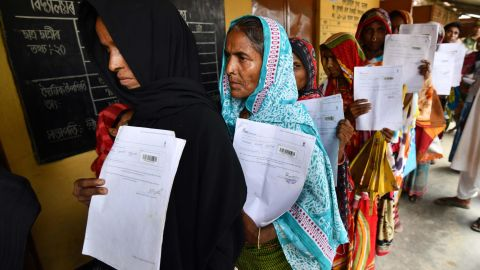 Residents hold their documents as they stand in a queue to check their names on the final list of National Register of Citizens.