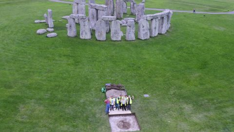 Researchers stand at the excavation site of Aubrey Hole 7, where cremated human remains were recovered at Stonehenge to be studied. New research suggests that 40% of 25 individuals buried at Stonehenge weren't from there -- but they possibly transported stones from west Wales and helped build it.