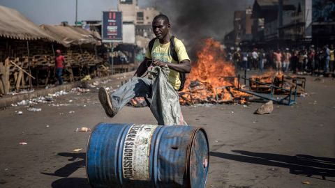 TOPSHOT - A supporter of Zimbabwean opposition MDC Alliance  push a barrel in front of a fire  in Harare on August 1, 2018, as protests erupted over alleged fraud in the country's election.Protests in Zimbabwe's historic elections turned bloody on August 1 as a man was shot dead during demonstrations over alleged vote fraud and the president appealed for calm. The man died after soldiers fired live ammunition during opposition protests in downtown Harare, AFP reporters saw. / AFP PHOTO / Luis TATOLUIS TATO/AFP/Getty Images
