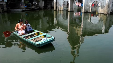 Claire Anne Tuazon takes her 8-year-old daughter, Genesis Tuazon, to school in a rowboat in the City of Malabon in the Philippines.