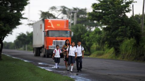 Silvia Alvarado, walks to school with her sister Rosario and brother Henry, accompanied by their mother Nuya, in the village of Metalio in El Salvador.