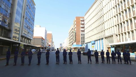 Zimbabwe police officers block the road leading to the opposition offices in Harare on Thursday.