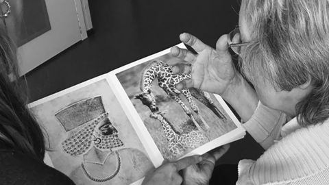 """An elderly woman looks at a """"Photographic Treatment"""" book and describes and compares what she sees. The pairing """"raises for me the question of function and aesthetics of geometry and why it is attractive to look at repetitive patterns -- because we find geometry highly aesthetic,"""" creator Laurence Aëgerter said."""