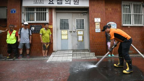 A firefighter sprays water in an alley of a residential district in Seoul to help ease the summer heat.
